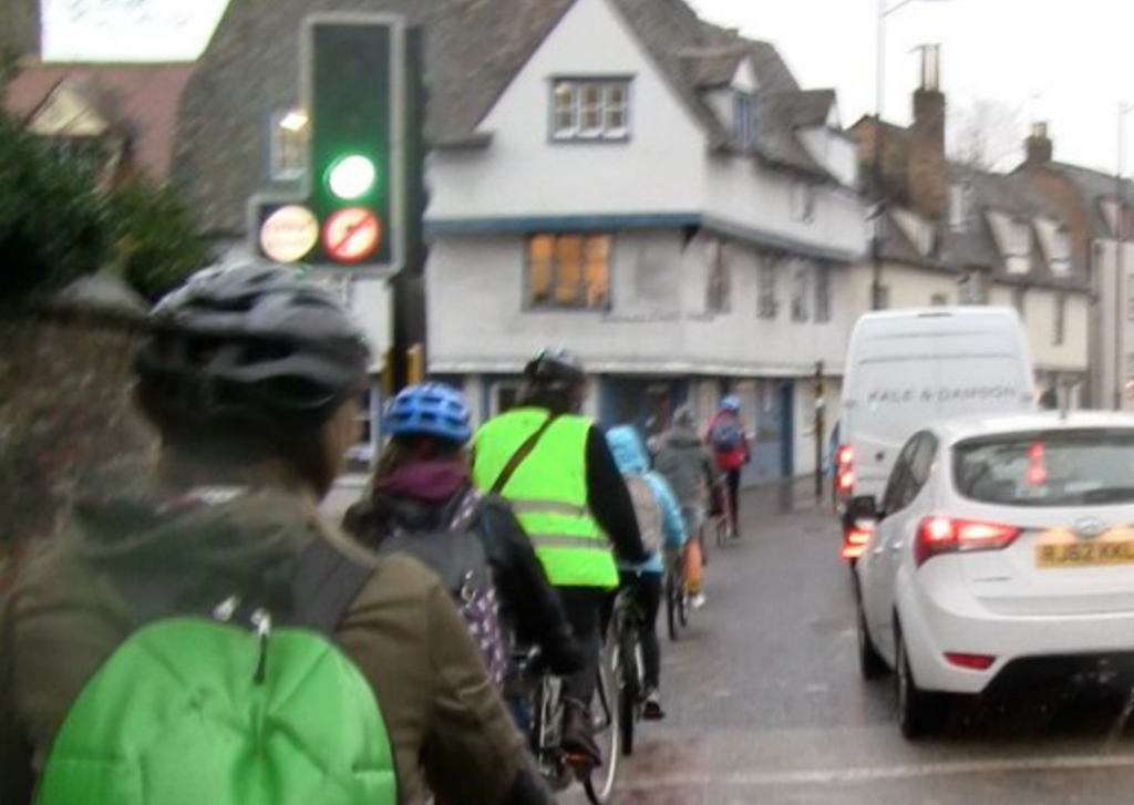 Cambridge cycling, image of motor vehicles next to cyclists.