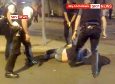 UK Police shock a man in Nottingham with a TASER while he is lying on the ground surrounded by four officers.