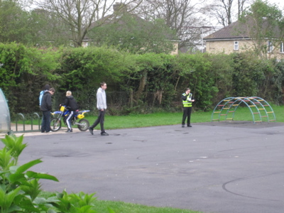 Youths with motorbike on the playground at St.Luke's School being stopped by PCSOs